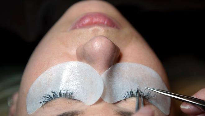 Lead esthetician Rachel Turner isolates eyelashes while applying eyelash extensions to Viktoriia Korin at Spavia Day Spa in Moorestown.