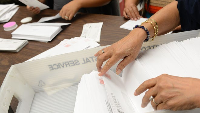 Department of Administration staff prepare income tax refund checks for mailing.
