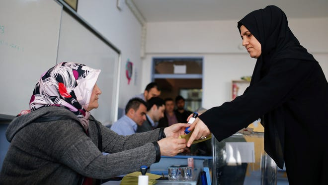 A voter takes a ballot from a member of an electoral committee, left, inside a polling station in Istanbul, Turkey, on Sunday, April 16, 2017.