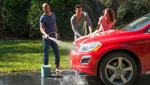 Family wash car at home.