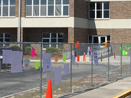 Students at Cypress Lake High School leave signs demanding greater gun control taped to the fence following their participation in the National School Walkout April 20, 2018.