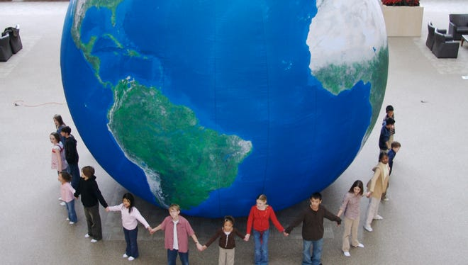 Children hold hands in a circle around Earth Adventure's inflatable walk-in Earth Balloon.