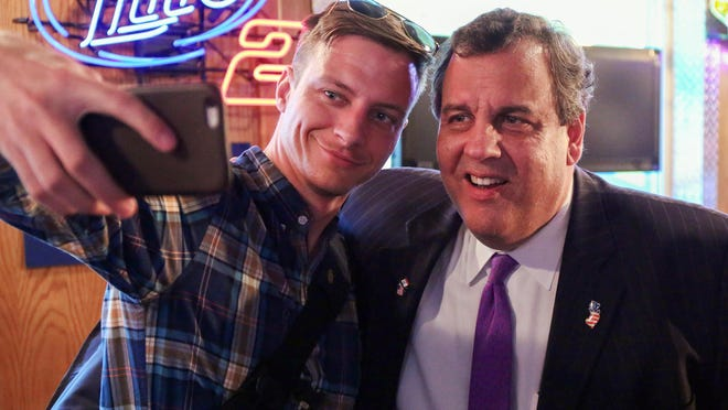 New Jersey Gov. and Republican presidential candidate Chris Christie pauses to pose for a selfie with a supporter after speaking at the Speedway Cafe in Newton, Iowa, on Oct. 21. (Bryon Houlgrave/The Des Moines Register via AP)