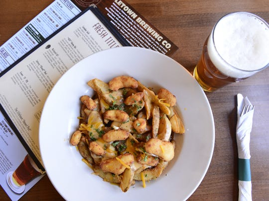 Poutine, often called Canadian nachos, gets a Green Bay twist (pub fries smothered with beef demi-glace, topped with white cheddar cheese curds and a drizzle of beer cheese fondue) at Titletown Brewing Co. The craft brewery and restaurant recently opened a new taproom where it features a wide variety of its beer.
