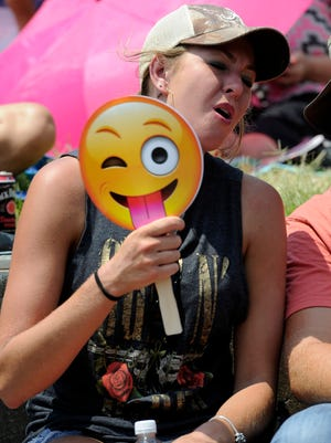 Molli McCormick of Trussville, Ala., tries to stay cool with a fan as she sings along to the music of Craig Campbell during the CMA Fest Sunday.