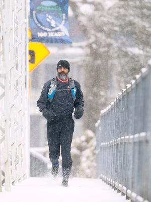 Jim Mastroianni of Califon runs across the historic Califon Bridge during a 10-mile run as the the fourth nor'easter in three weeks hits New Jersey, bringing heavy snow and winds.