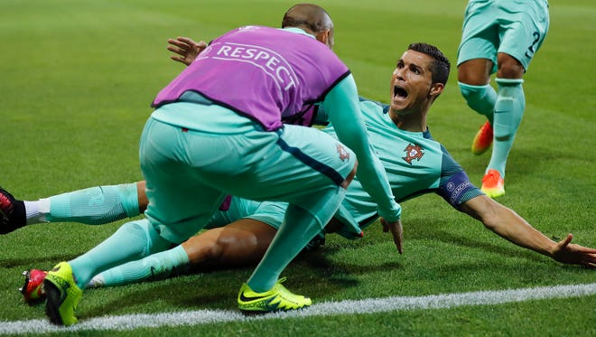 Portugal's Cristiano Ronaldo celebrates after scoring his side's first goal during the Euro 2016 semifinal soccer match between Portugal and Wales, at the Grand Stade near Lyon, France Wednesday.