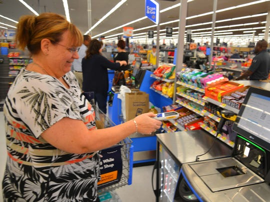 Theresa Schindler checks out at the Titusville Walmart. Walmart has started a new service called Scan & Go to make shopping easier and checkout quicker.  You pick up a handheld scanner that fits in the cart, scan your items as you shop and then just scan and pay at the self checkout terminal.
