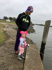 Eric Guidry teaches daughter Avery, 3, to fish on a very cold and windy day at Cypremort Point State Park.