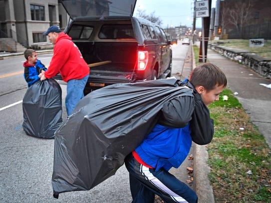 Miguel Urrutia, 10, hauls a bag full of toys as his