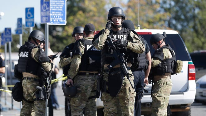 Law enforcement officers dressed in tactical gear prepare to aid in the search of an assailant, in Auburn, Calif.,  who shot three sheriff's deputies in two California counties Friday.