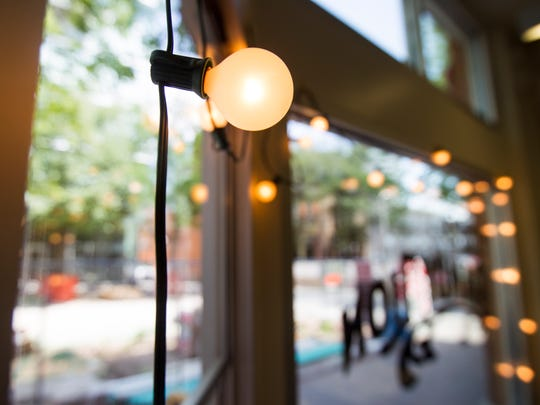 Lights hang from the front window inside Dandy Lion on Tuesday, July 3, 2018. Dandy Lion is now open and will be expanding their hours after pedestrian mall construction is completed.