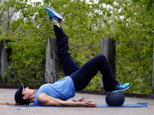 Catherine Andersen shows the medicine ball hip bridge  exercise.