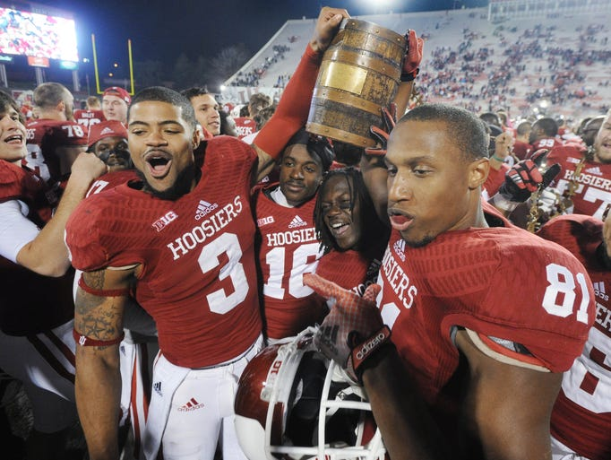 Cody Latimer, 3, and Duwyce Wilson and other IU players celebrate winning the bucket. IU defeated Purdue 56-36 to regain the Old Oaken Bucket in a football game Saturday November 30, 2013 in Bloomington.