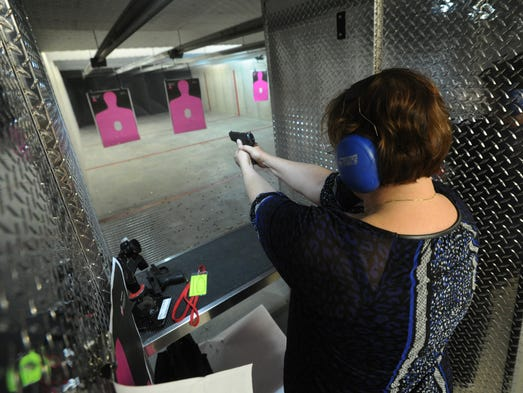 Laurie Spear, of Westfield, shoots a handgun during