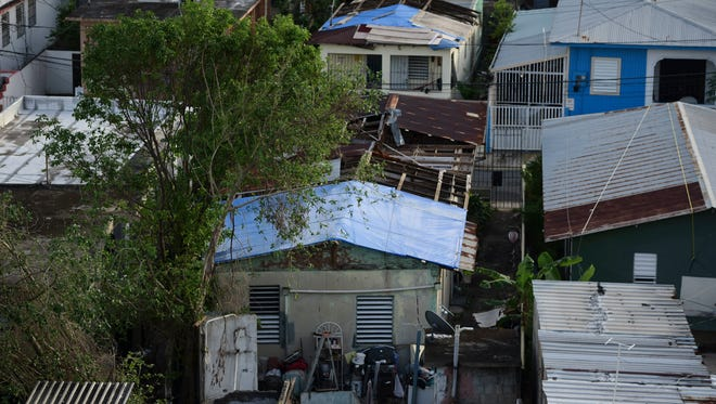 In this Nov. 15, 2017 photo, some roofs damaged by Hurricane Maria have awnings installed in El Gandúl neighborhood, in San Juan, Puerto Rico.