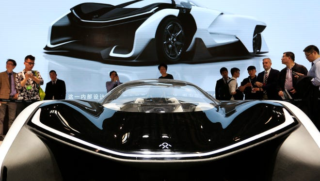 Visitors look at Faraday Future's single-seat concept car FFZero1at Auto China 2016 motor show in Beijing