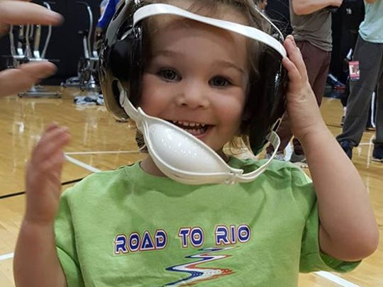 Three-year old Evelyn Provisor, daughter of two-time Olympian Ben Provisor, poses with wrestling headgear.