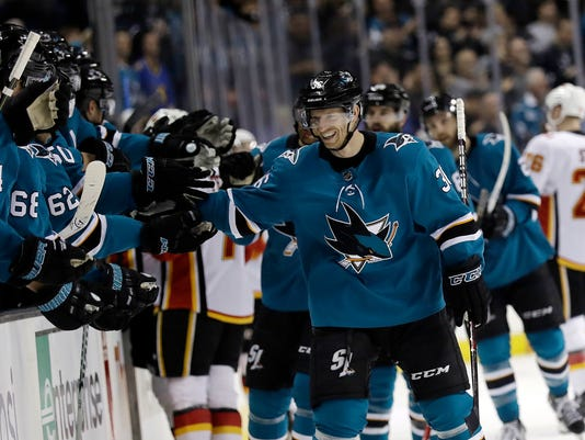 San Jose Sharks' Jannik Hansen, right, celebrates with teammates after scoring against the Calgary Flames during the first period of an NHL hockey game Saturday, March 24, 2018, in San Jose, Calif. (AP Photo/Marcio Jose Sanchez)