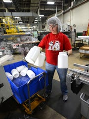 NEW Plastics machine operator Meg Kline pulls freshly molded plastic bottles from the machine output line before stacking them on pallets on Dec. 9.