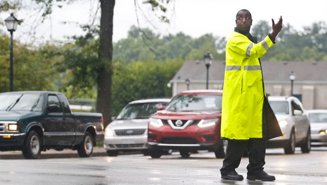 New Albany Police traffic officer Paul Speights directs traffic on Spring Street near the I-64 onramp to the Sherman Minton Bridge Wednesday morning as the closure of I-65 created heavy congestion as motorists tried to access the Sherman Minton Bridge to cross into Louisville. Aug. 19, 2014