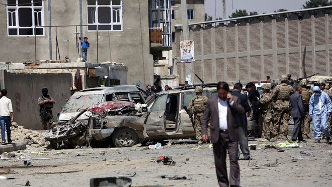 U.S. and Afghan security forces inspect the site of suicide attack near an international airport in Kabul, Afghanistan, Sunday, May 17, 2015.