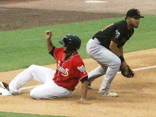 Diego Goris, left, of the El Paso Chihuahuas slides