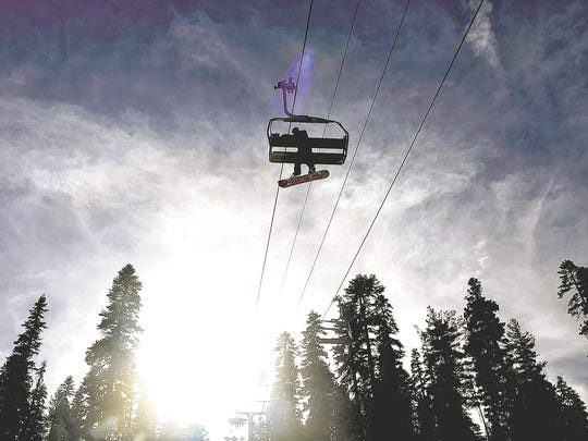 A snowboarder rides the Comstock Lift at Northstar California.