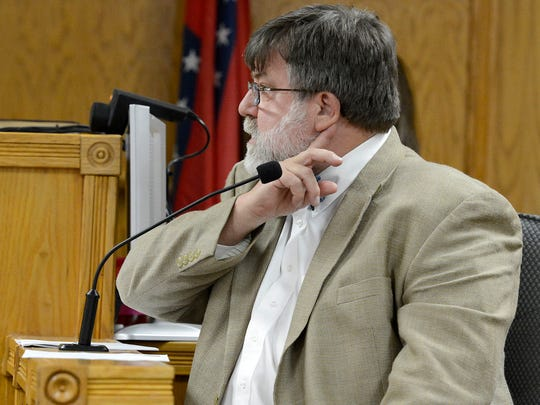 Arkansas Chief Medical Examiner Dr. Charles Kokes demonstrates the area of the neck that was cut on Dr. David Millstein's body during testimony in the Gary Wayne Parks murder trial in March 2013.