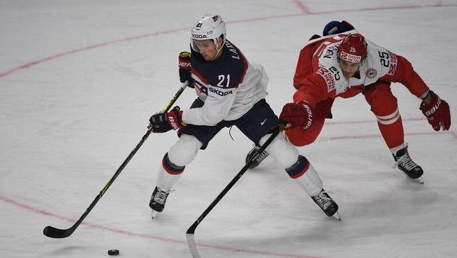Denmark´s Oliver Lauridsen and the U.S.'s Dylan Larkin vie for the puck during a IIHF ice hockey world championship first-round match in Cologne, Germany on May 7, 2017.