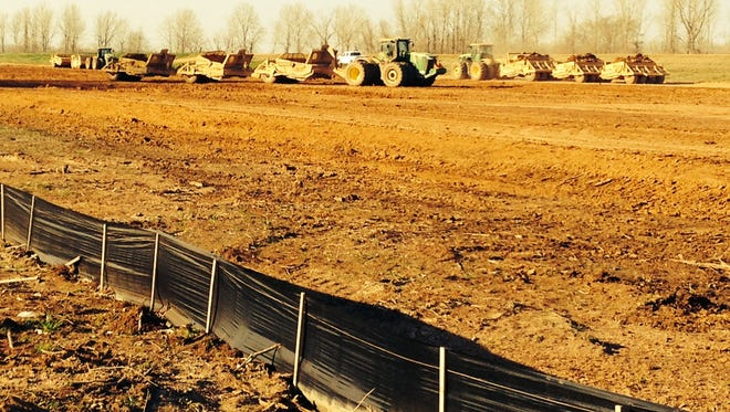 Crews build a berm to strengthen Red River levees.