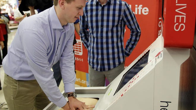 Sean Ferguson, left, practices CPR on a kiosk like the one Matt Lickenbrock, right, learned on two days before saving Ferguson's life, during a news conference at the Indianapolis International Airport in Indianapolis.