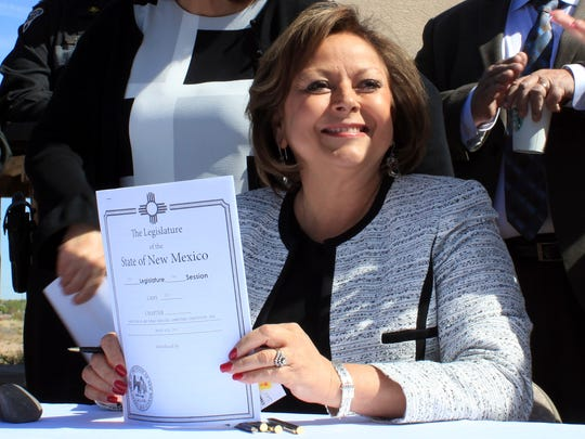 In this April 6, 2017, file photo, New Mexico Gov. Susana Martinez holds signed legislation that expands access to the overdose antidote naloxone during a ceremony at a substance abuse treatment center for youth in Albuquerque, N.M. With the signing, New Mexico became the first state to require all state and local law enforcement officers to be equipped with naloxone. The measure also requires treatment clinics to educate their patients and provide two doses of naloxone and a prescription for the overdose-reversal drug.