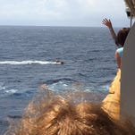 Three Cuban refugees cling to a capsized boat last Thursday in the Atlantic Ocean.