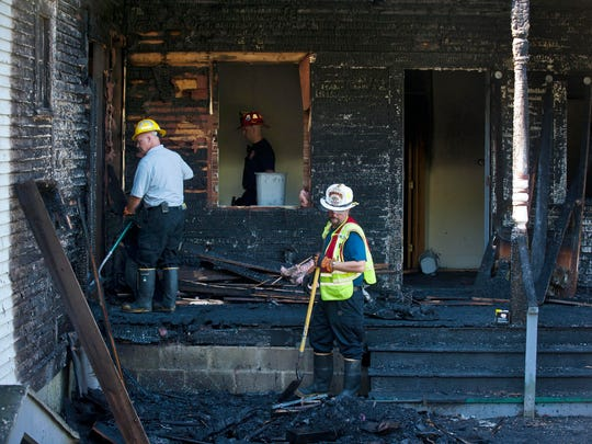 Responders sift through the aftermath of a suspected arson fire on South Main Street in Barre on Tuesday.