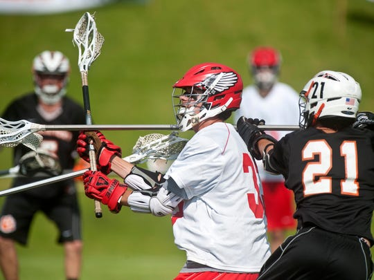 CVU's Elliott Mitchell (left) is pressured by Middlebury's Austin Robinson in Hinesburg on Tuesday, June 10, 2014