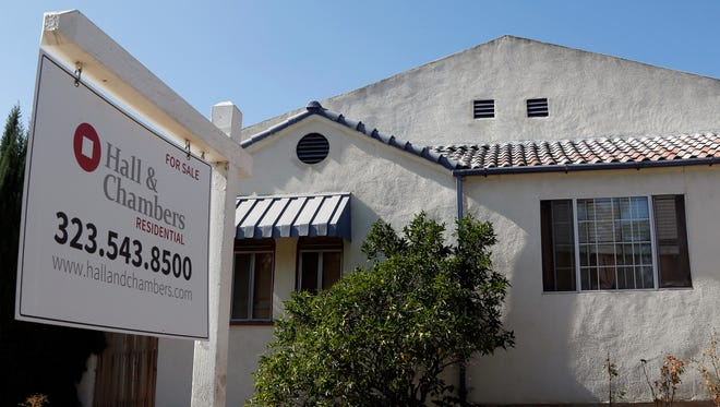 A realty sign hangs outside a home for sale in Los Angeles.