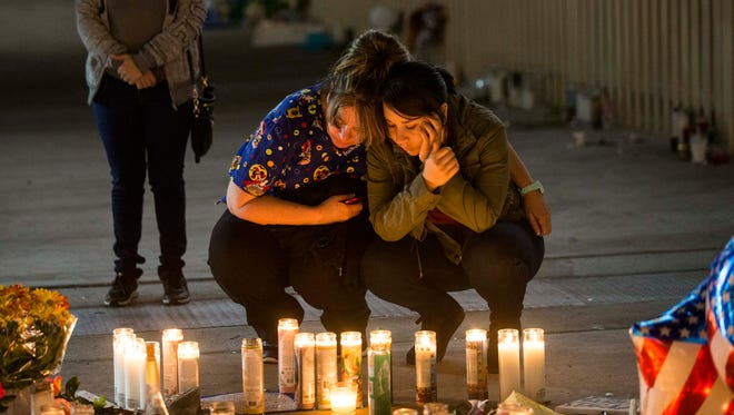 Sara Rivero, on right, with her mom Laura Rodriguez, in center and Gisell Rivera, her step mother,  burn a candle at the memorial site on Las Vegas Blvd, for friends who died at the concert.