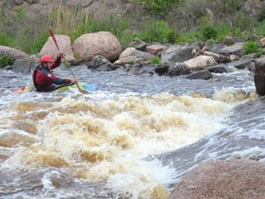 Kayakers practice their freestyle moves on the course