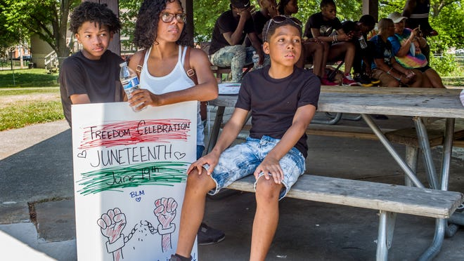 Kamia Moore watches, flanked by her sons, Kamari, 9, right, and Kamelion, 13, as people arrive Friday, June 19, 2020, for a block party celebration at Martin Luther King Jr Park in Peoria of Juneteenth, the day that in 1865 the last slaves in the United States were freed. DAVID ZALAZNIK/JOURNAL STAR