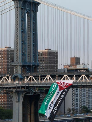 Demonstrators hang a protest flag from the south side of the Manhattan Bridge as a pro-Palestinian rally (not pictured) makes its way across the nearby Brooklyn Bridge, Wednesday in New York.