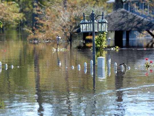 Cars and homes on Fork Retch Court in Mullins remained flooded over on Thursday after Hurricane Matthew hit the coast. Thursday, October 13, 2016.