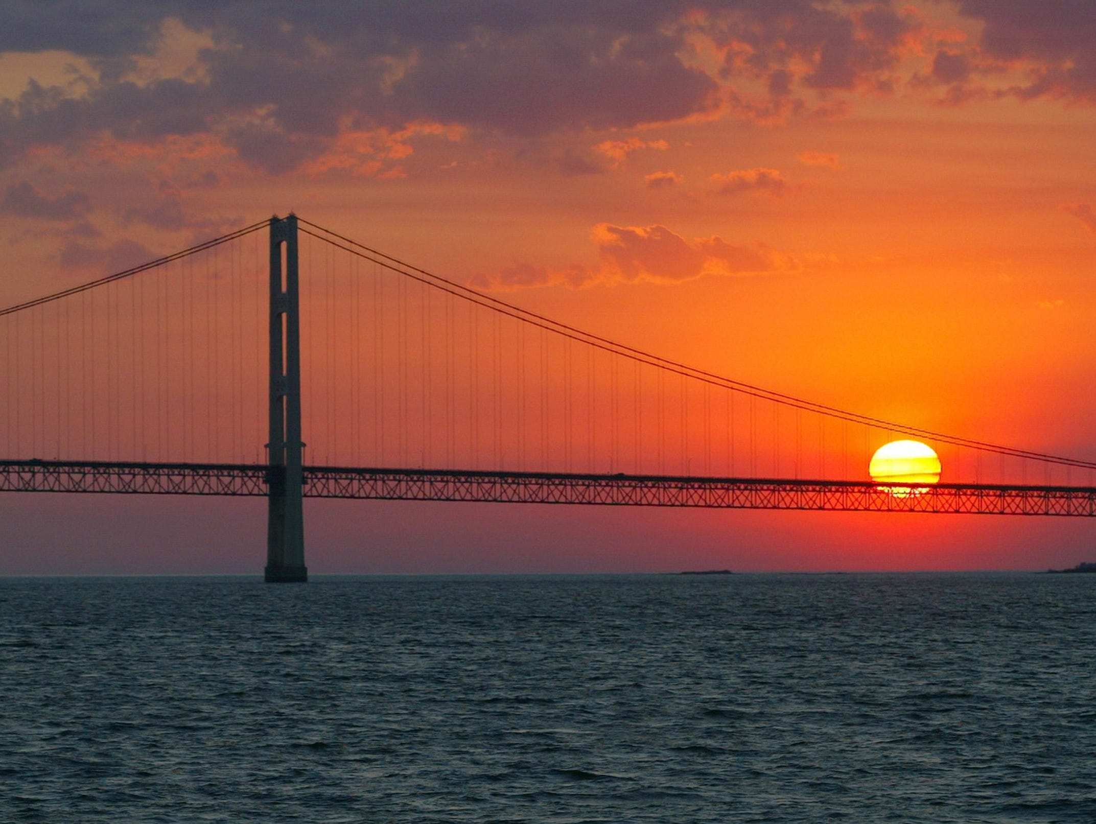The sun sets over Lake Michigan in Mackinaw City, Mich. State officials say they've heard from two operators interested in raising rainbow trout in floating enclosures in Lake Michigan and Lake Huron.