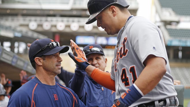 Manager Brad Ausmus greets Victor Martinez in the dugout after a homer. Entering today's scheduled regular-season finale, the Tigers are in the race.