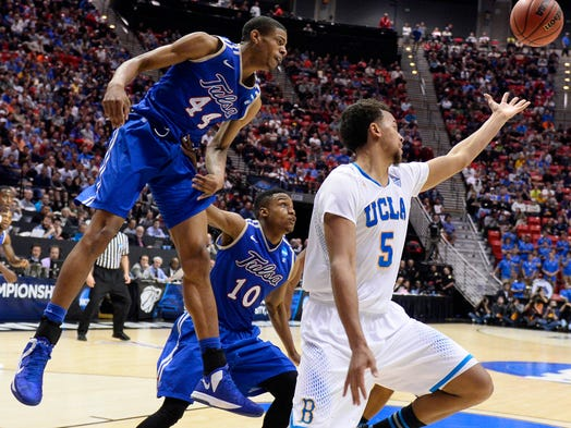 UCLA Bruins guard/forward Kyle Anderson reaches for the ball as Tulsa Golden Hurricane Brandon Swannegan, left, and James Woodard look on at Viejas Arena.