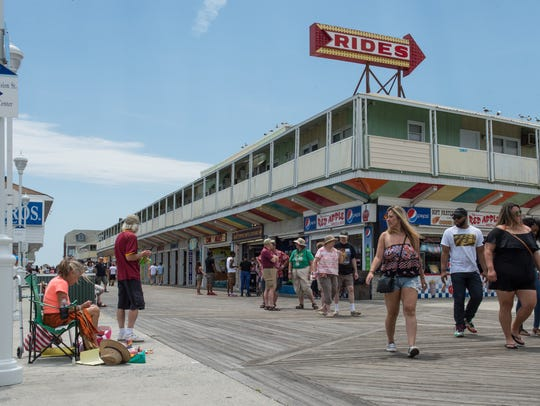 Beachgoers make their way down the boardwalk in Ocean
