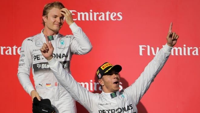 Mercedes driver Lewis Hamilton (below) celebrates after winning the Formula One U.S. Grand Prix on Sunday as teammate Nico Rosberg, who finished second, joins him on stage.