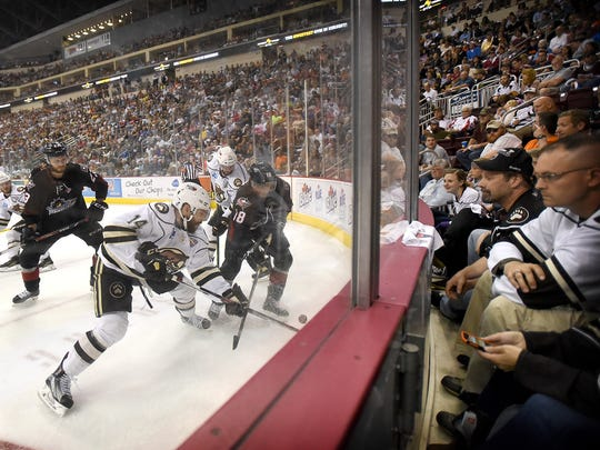 Hershey Bear Ryan Bourque (14) battles Lake Erie Monster T.J. Tynan (18) for possession. Despite a run in the third period to pull within  a goal, the Hershey Bears dropped game two of the Calder Cup finals in Hershey Friday night by a 5-3 score.
