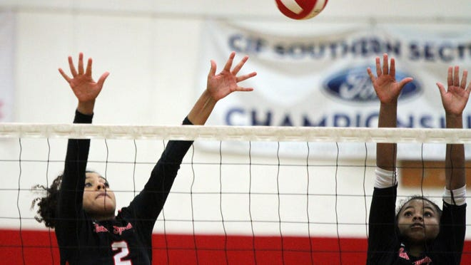 Palm Springs' Hannah Wright, left, and Maribel Wright go up for a block during the game against Xavier Prep at Palm Springs High School in Palm Springs on Thursday, October 1, 2015.