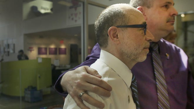 James Ryder puts his arm around his husband, Frank Colasonti Jr., at a party Sunday at Affirmations community center in Ferndale to celebrate the one-year anniversary of their legal marriage in Michigan.